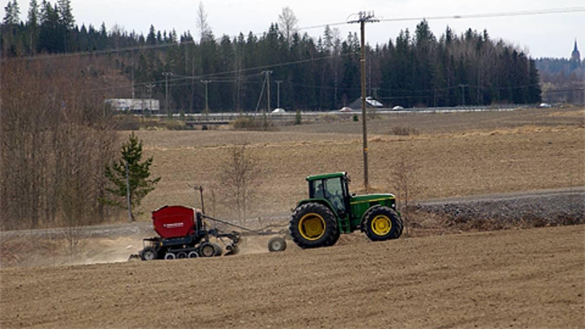 Traktori vetää pellolla kylvökonetta.