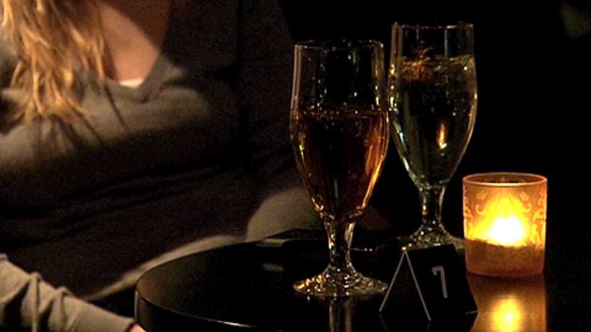 Nainen ravintolassa, pöydällä kaksi lasillista siideriä ja kynttilä.
