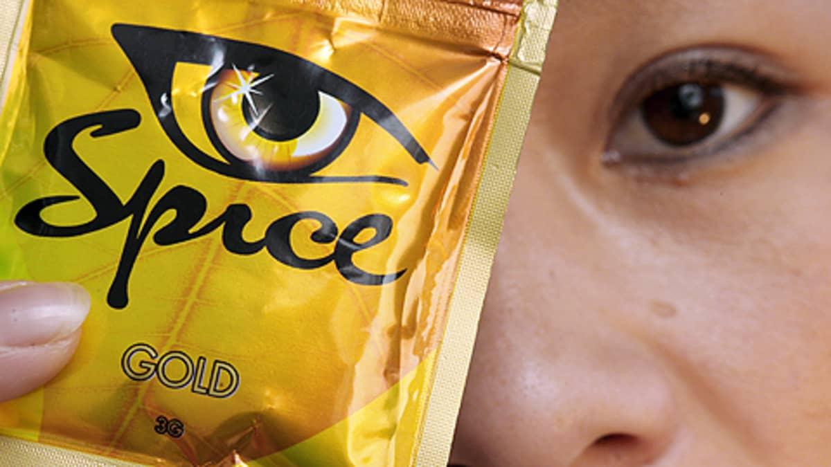 Nainen pitää Spice-huumausainepakettia kasvojensa edessä.