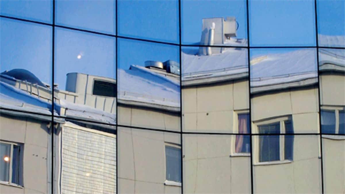 Kerrostalo heijastuu ikkunoista.