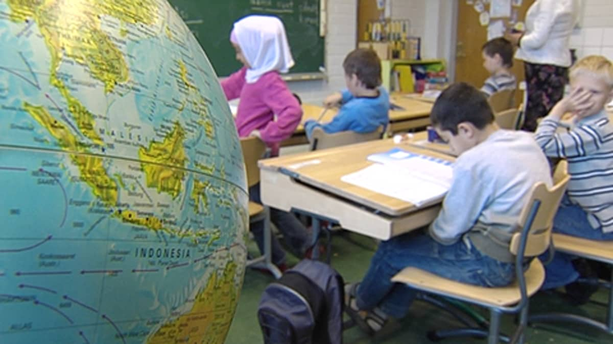 Oppilaita ala-asteen luokkahuoneessa, kuvan etualalla karttapallo.