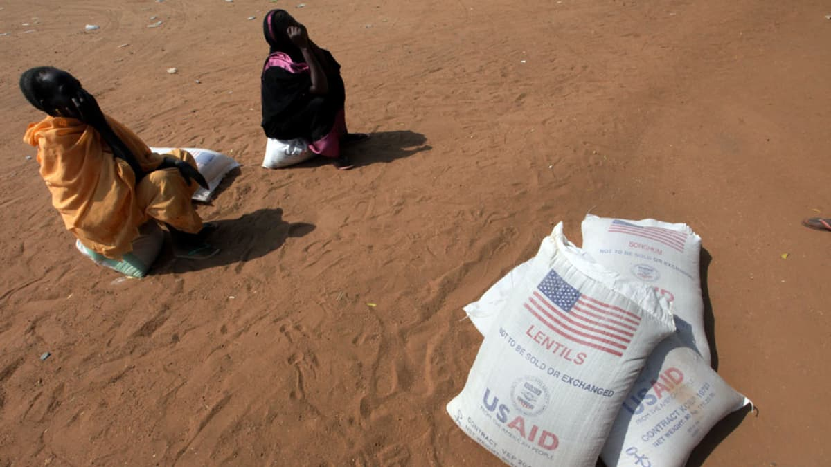 Kaksi sudanilaista naista odottavat ruokaa jaettavaksi linssisäkkien vieressä.