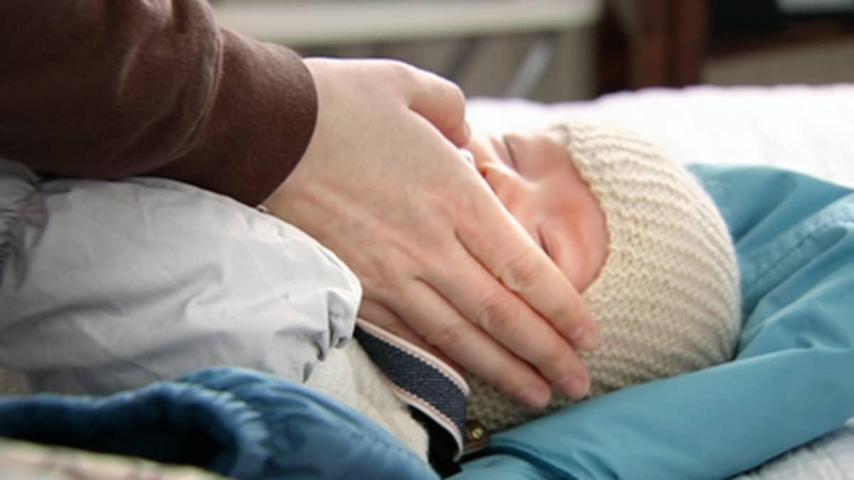 Äidin käsi lapsen poskella