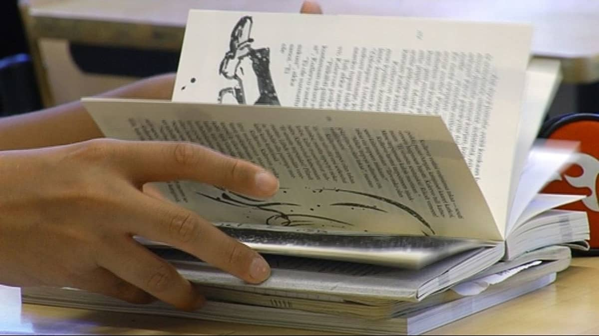 Nuori selaa kirjaa.