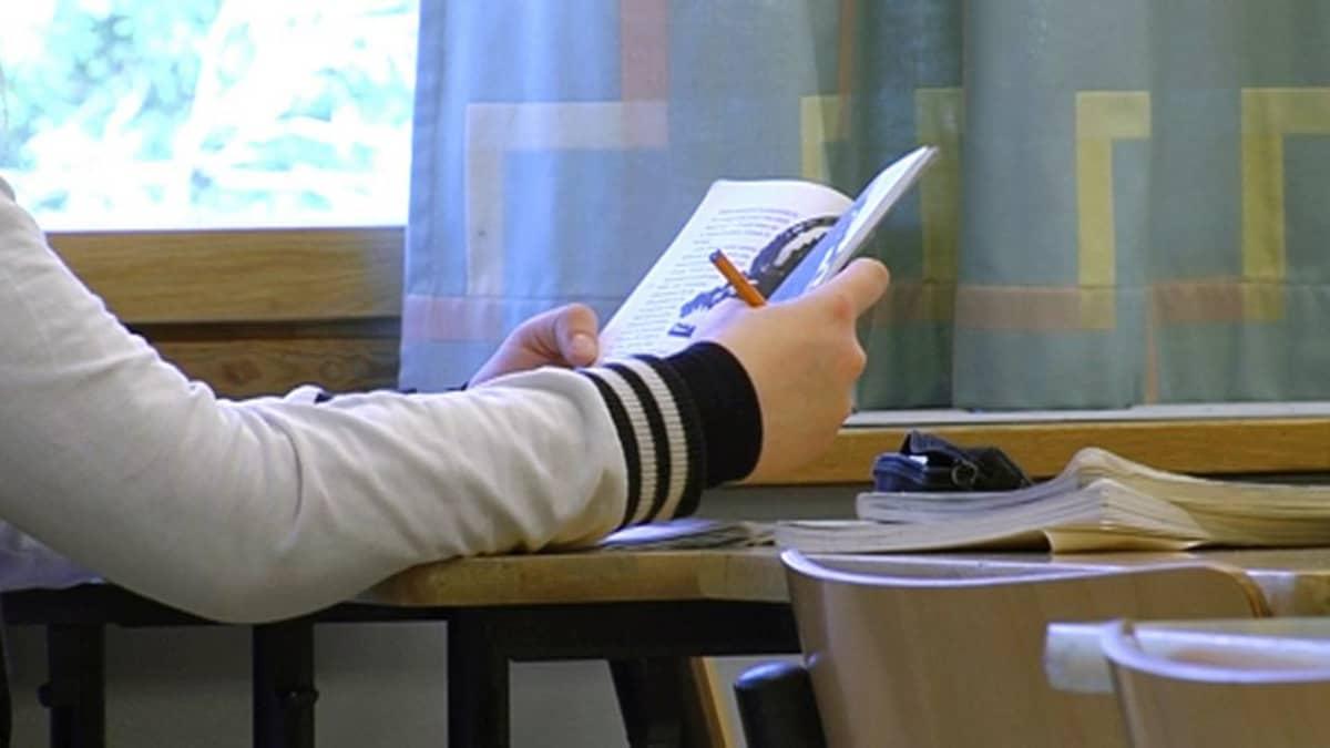 Nuori lukee luokassa.