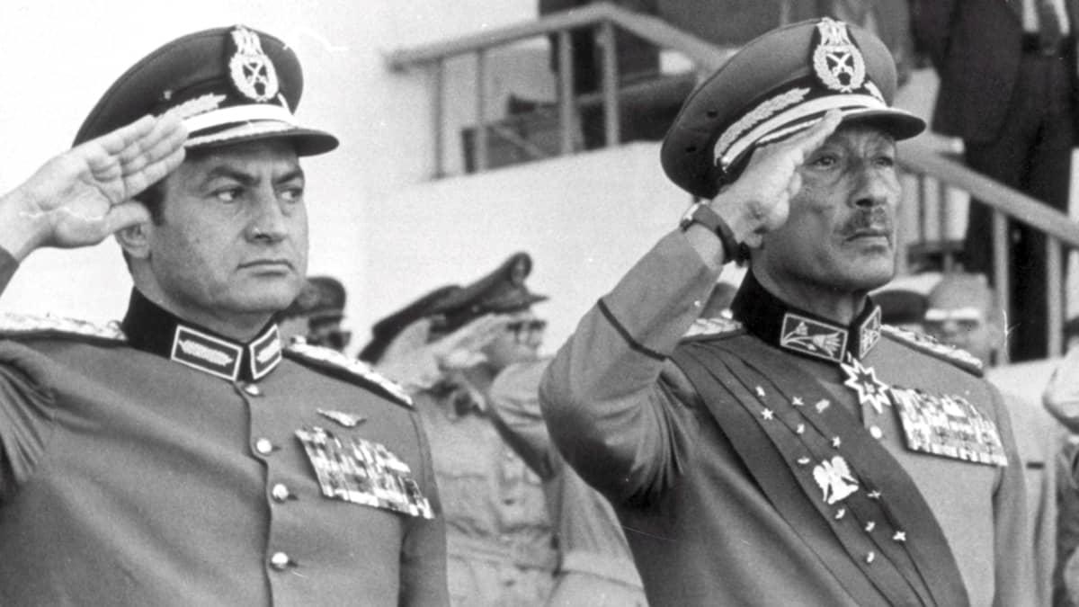Hosni Mubarak ja Anwar Sadat sotilasuniformuissa kädet lipassa vuonna 1981.