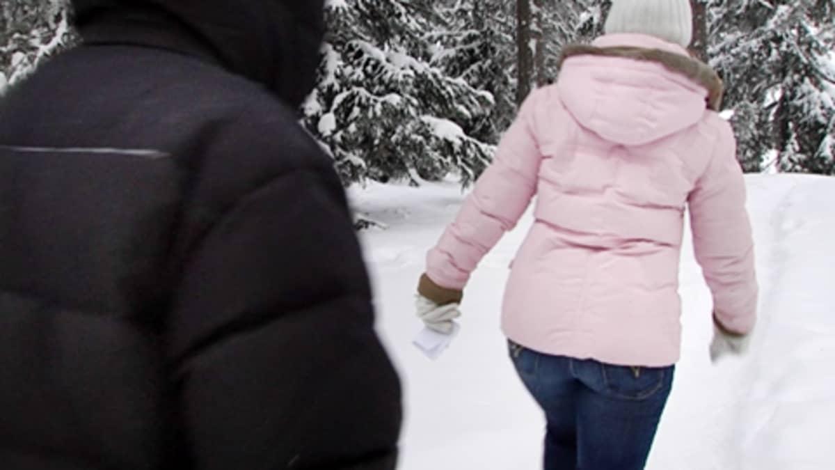 Mustaan toppatakkiin pukeutunut henkilö seuraa naista lumisessa metsässä.