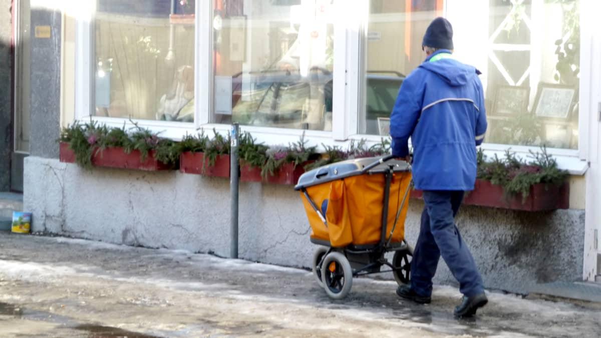 Kuvassa postinjakaja liukkaalla kadulla.
