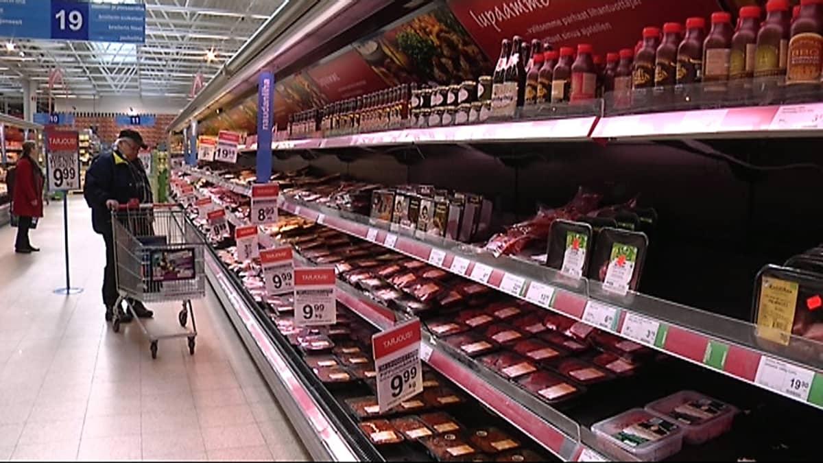Asiakas lihahyllyllä ruokakaupassa.