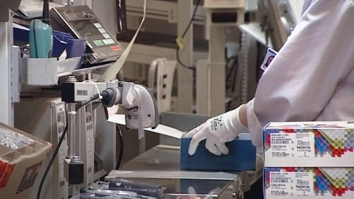 Työntekijä pakkaa puhelimia Nokian Salon tehtaalla.