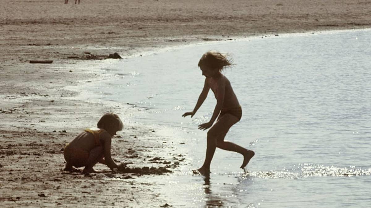 Kaksi lasta leikki vedenrajassa