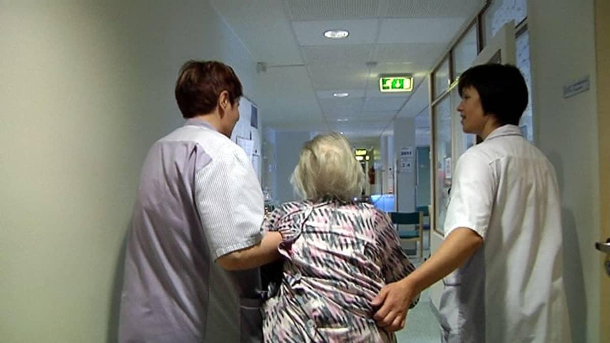 Iäkäs nainen sairaalan käytävällä. Kaksi hoitajaa kannattelee käsivarsista.
