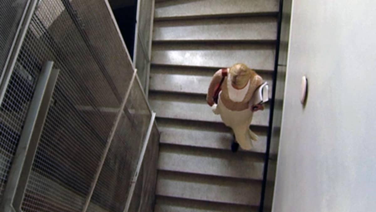 Nainen kerrostalon rappukäytävässä.