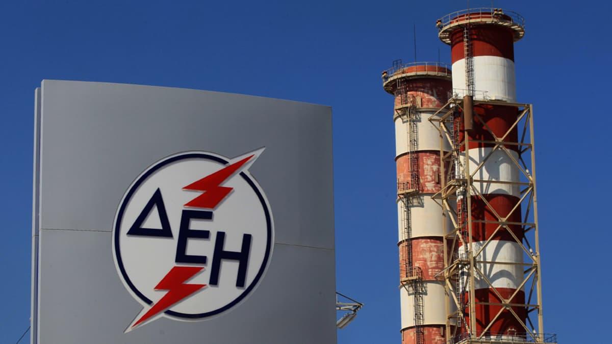 Kaksi punavalkoista tornia taustalla, kuvan etualalla harmaa seinämä, jossa on DEI-logo.
