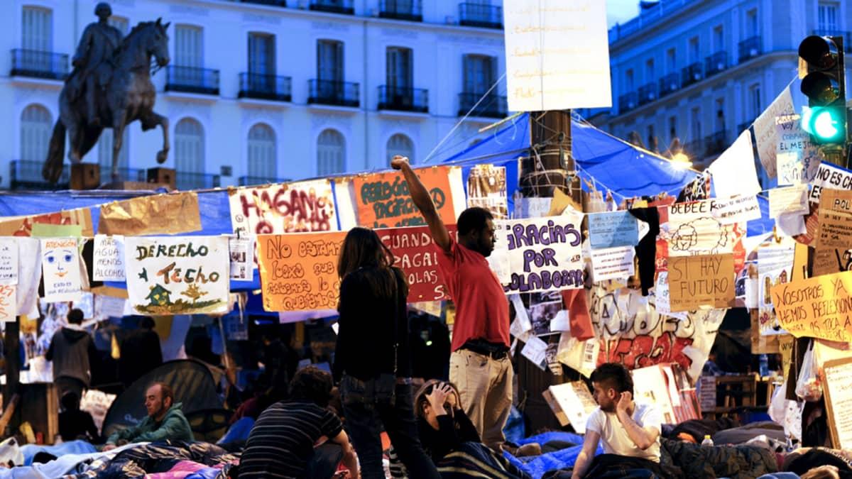 Mielenosoittajat heräilevät valtaamaltaan aukiolta Madridissa.