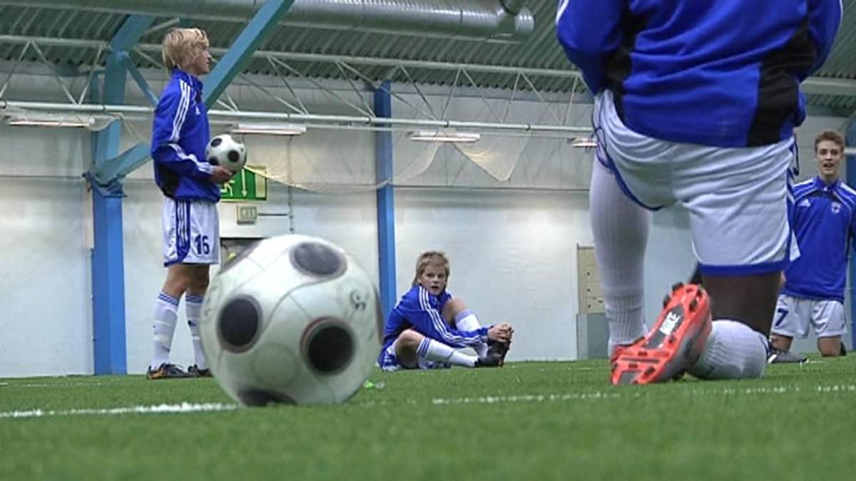 Nuoria jalkapalloilijoita harjoituksissa sisähallissa