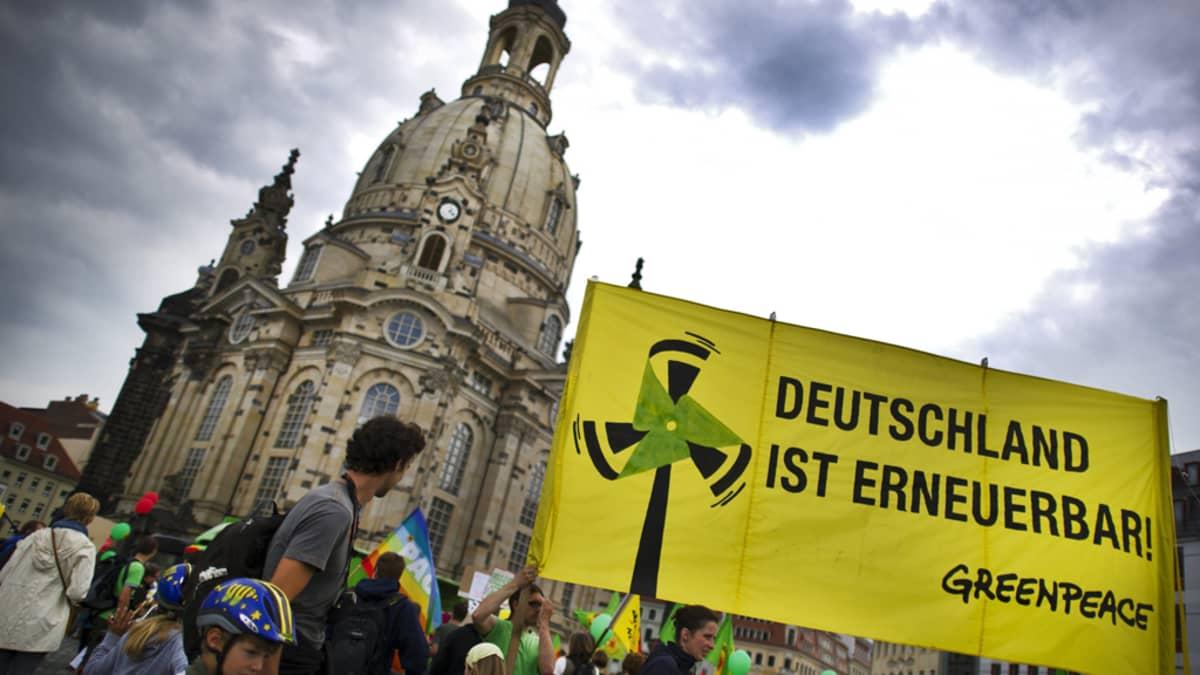 Greenpeacen ydinvoiman vastainen lippu edessä, taustalla Dresdenin vanha kirkko ja tumma taivas.