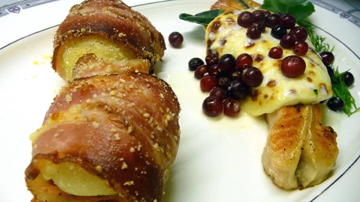 Pekoniin käärittyä perunaa, lohen päällä leipäjuustokiekko ja karpaloita aseteltuna lautaselle annokseksi.