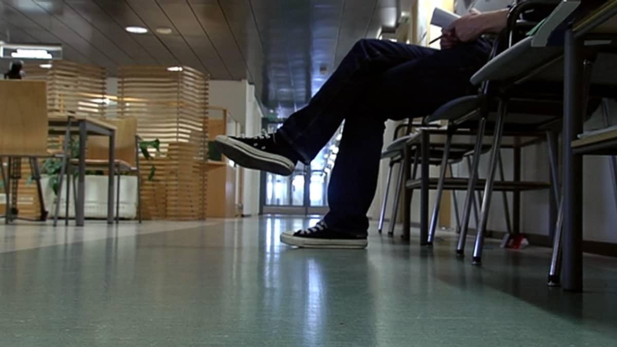 Mies odottaa sosiaalivirastossa asiointivuoroaan