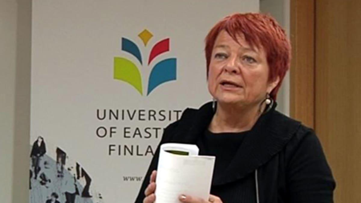 Tarja Cronberg puhuu Itä-Suomen yliopistossa paperinivaska kädessään.