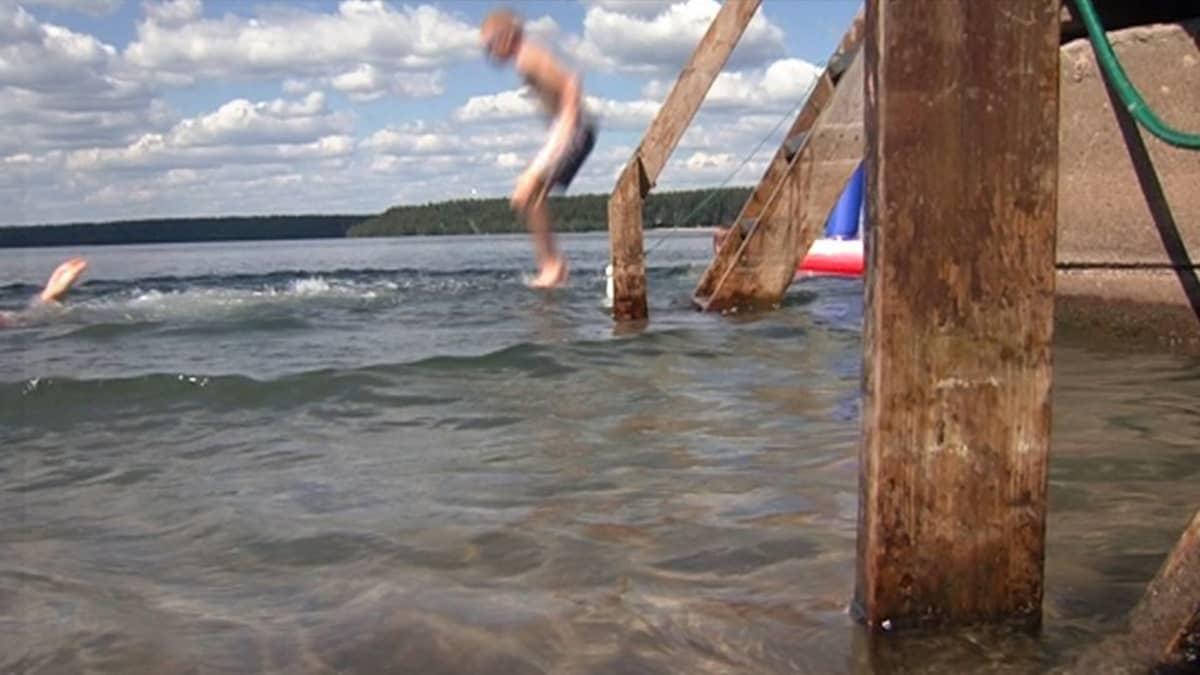 Poika hyppää laiturilta järveen.