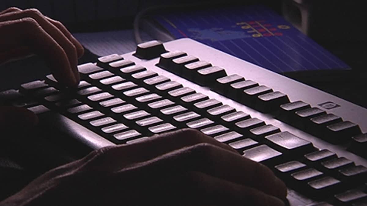 Tuntemattoman henkilön kädet tietokoneen näppäimistöllä