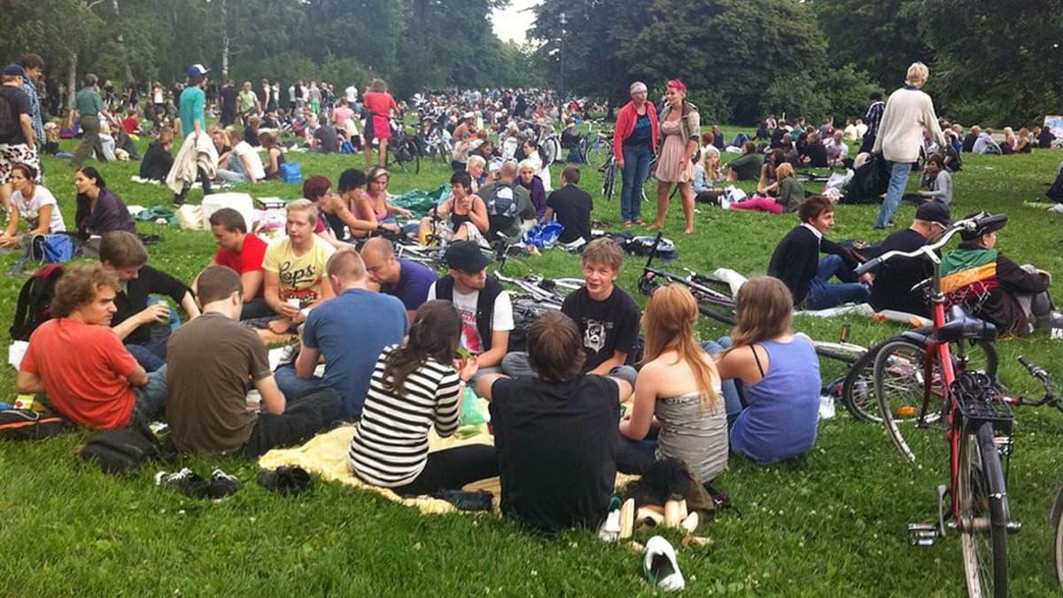 Ihmisiä Turun Kupittaanpuiston Botellón-piknikillä.