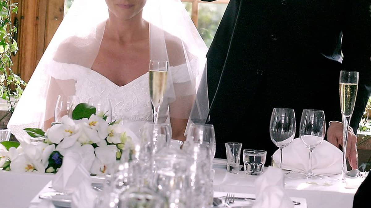 Morsian ja sulhanen hääjuhlapöydän äärellä