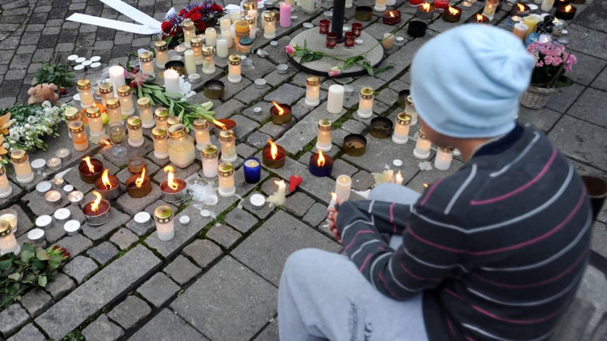 Poika istuu ja katselee kynttilöitä ja lyhtyjä, jotka on tuotu surmattujen ihmisten muistoksi.