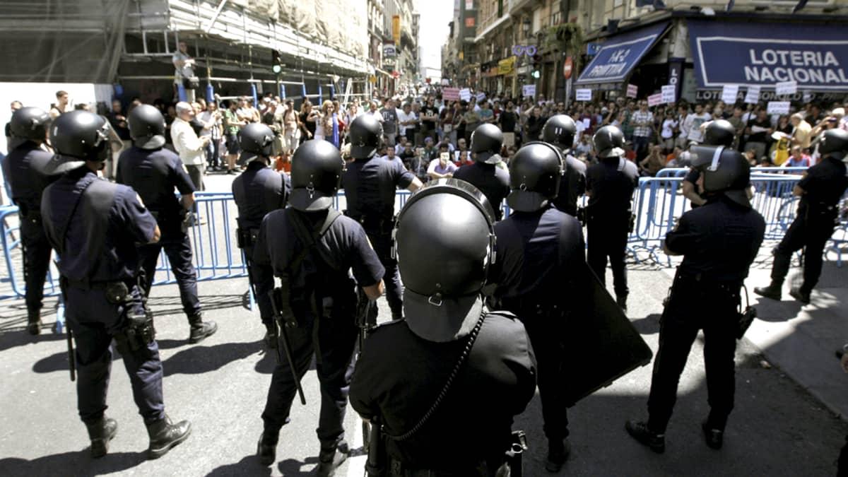 Mellakkapoliiseja ja mielenosoittajia Puerta del Solin aukiolla 4. elokuuta.