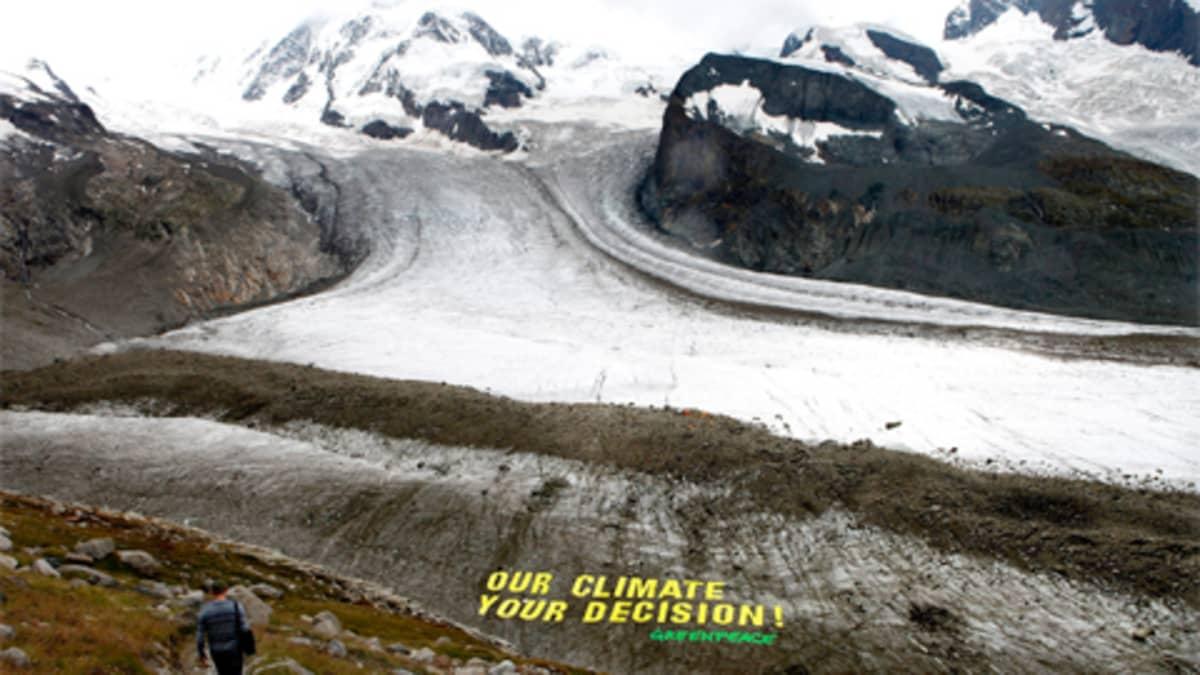 Vaeltaja 2600 metrin korkeudessa Gornerin jäätiköllä Sveitsissä. Edessä Greenpeacen jättimäinen kannanotto ilmastonmuutokseen.