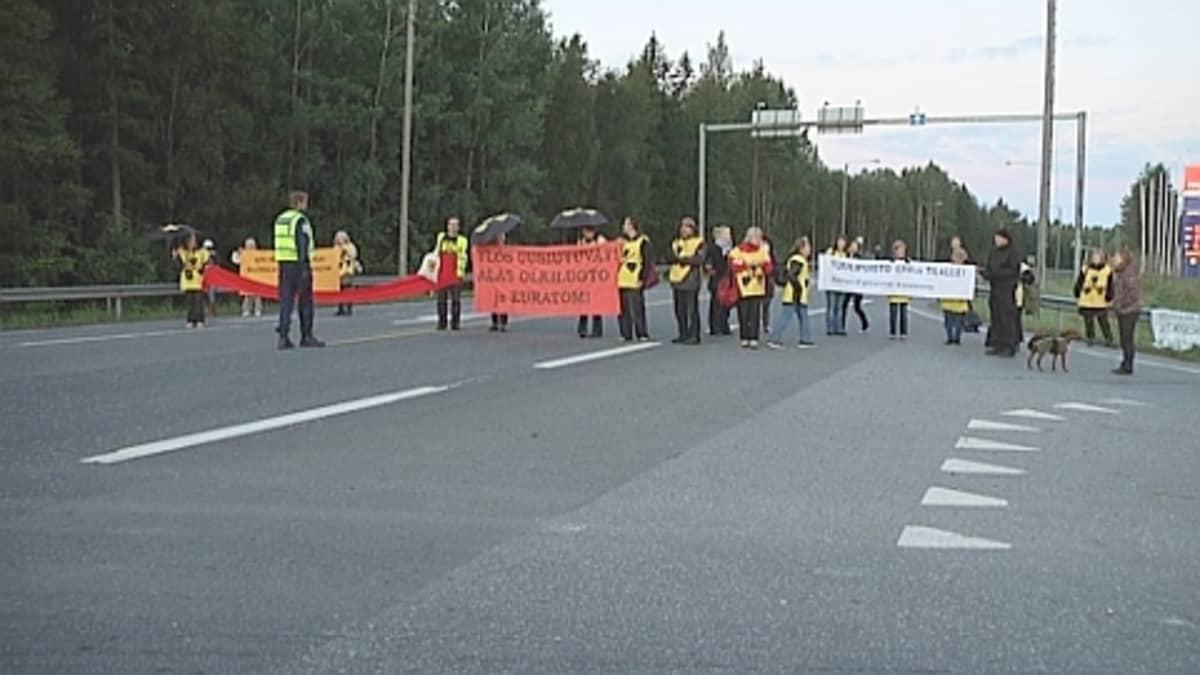 Mielenosoittajia tiellä.