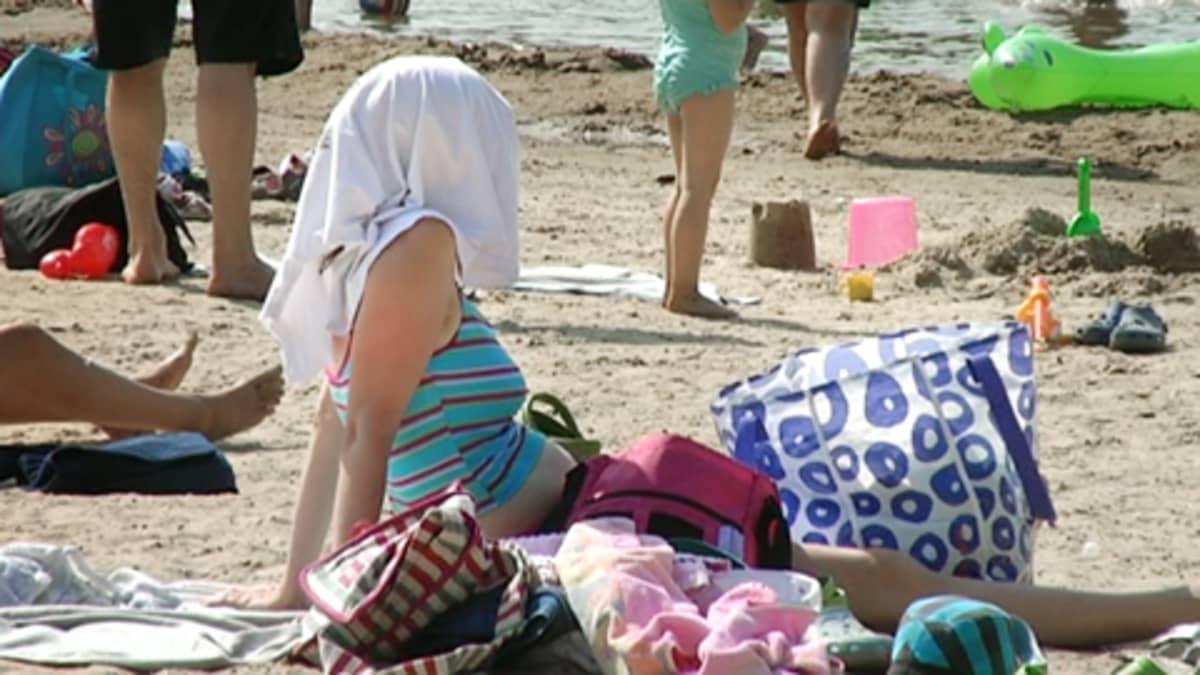 Päänsä  pyyhkeellä auringon paahteelta suojannut nainen istuu uimarannalla.