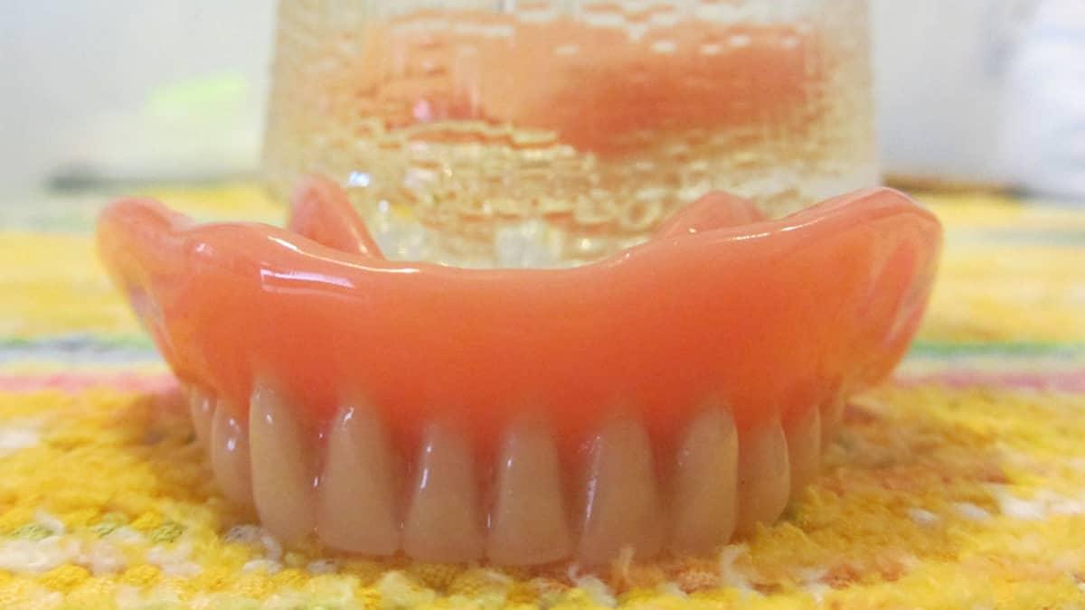 Kuvassa etualalla hammasproteesi, taustalla juomalasi