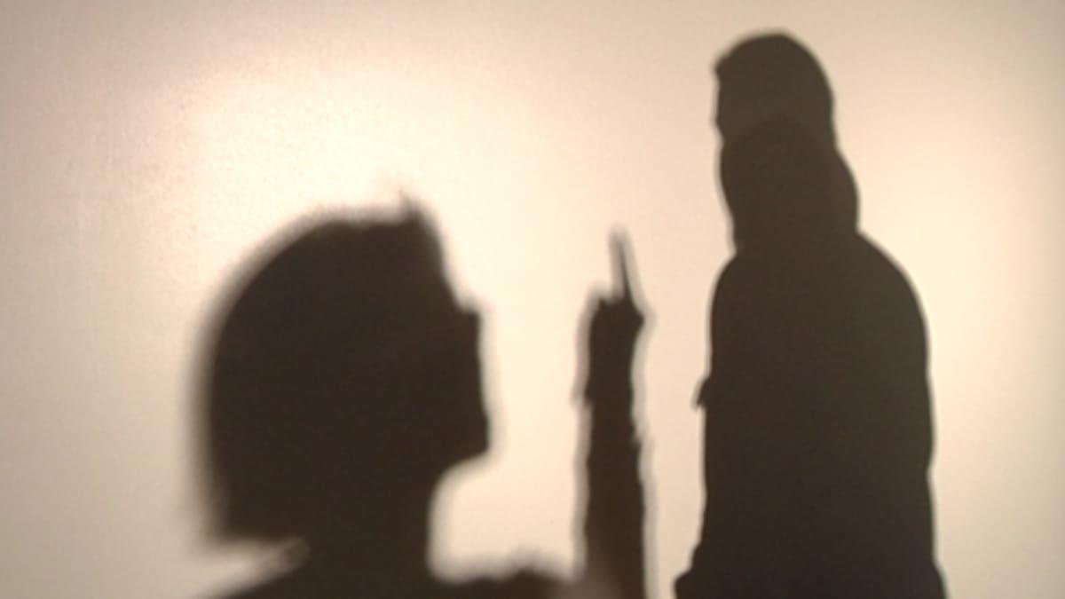 Varjokuva tytöstä, joka näyttää keskisormea toiselle ihmiselle.