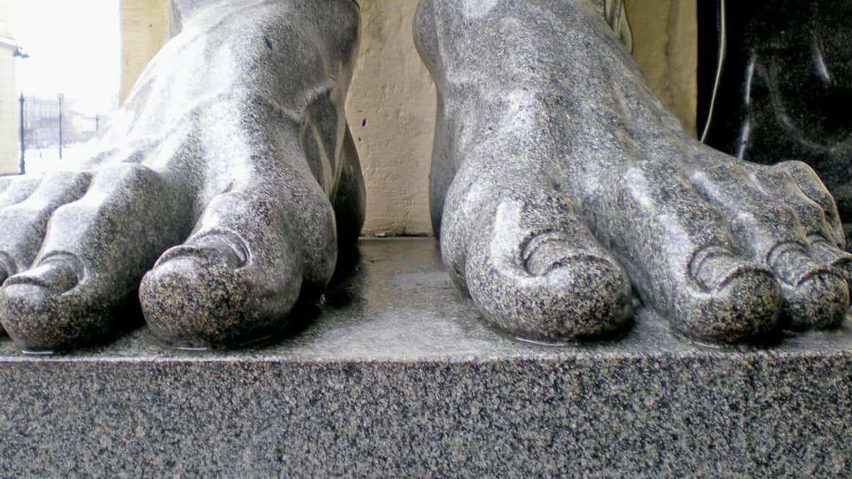 Harmaat patsaan paljaat jalat.
