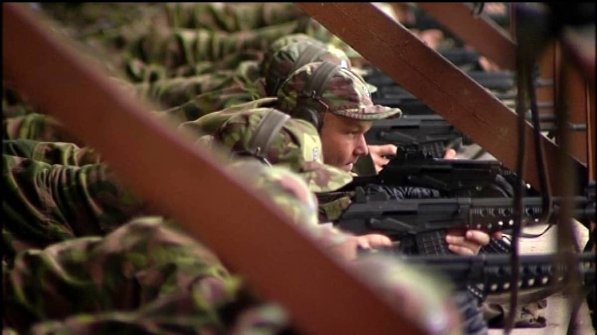 Maastopukuisia miehiä kertausharjoitusten ammunnoissa.