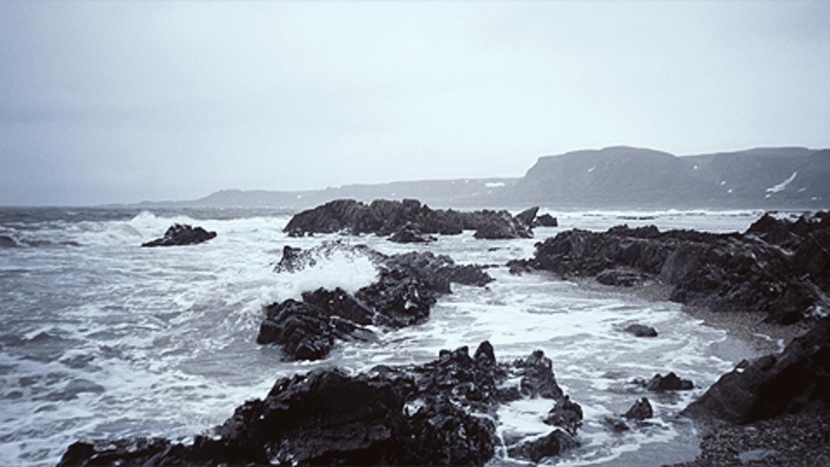 Jäämeren rantakivikko. Aallot lyövät rantaan. Pilvinen sää.