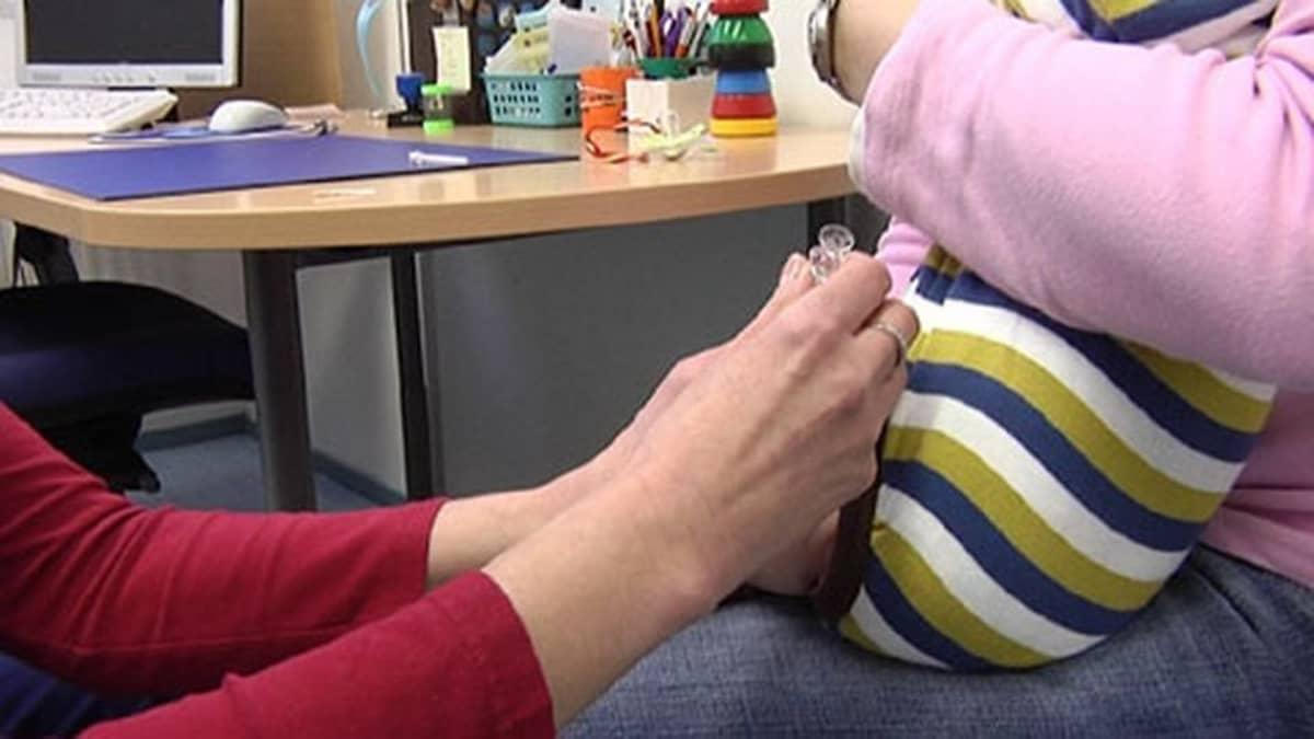 Kuvassa äidin sylissä olevaa lasta rokotetaan vasempaan reiteen.