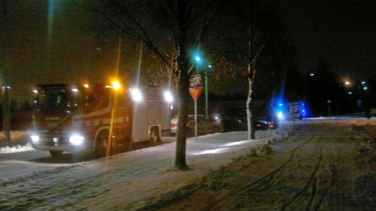 Paloauto ja ambulanssi hälytysvaloissa kahden henkilöauton kolaripaikalla risteyksessä.