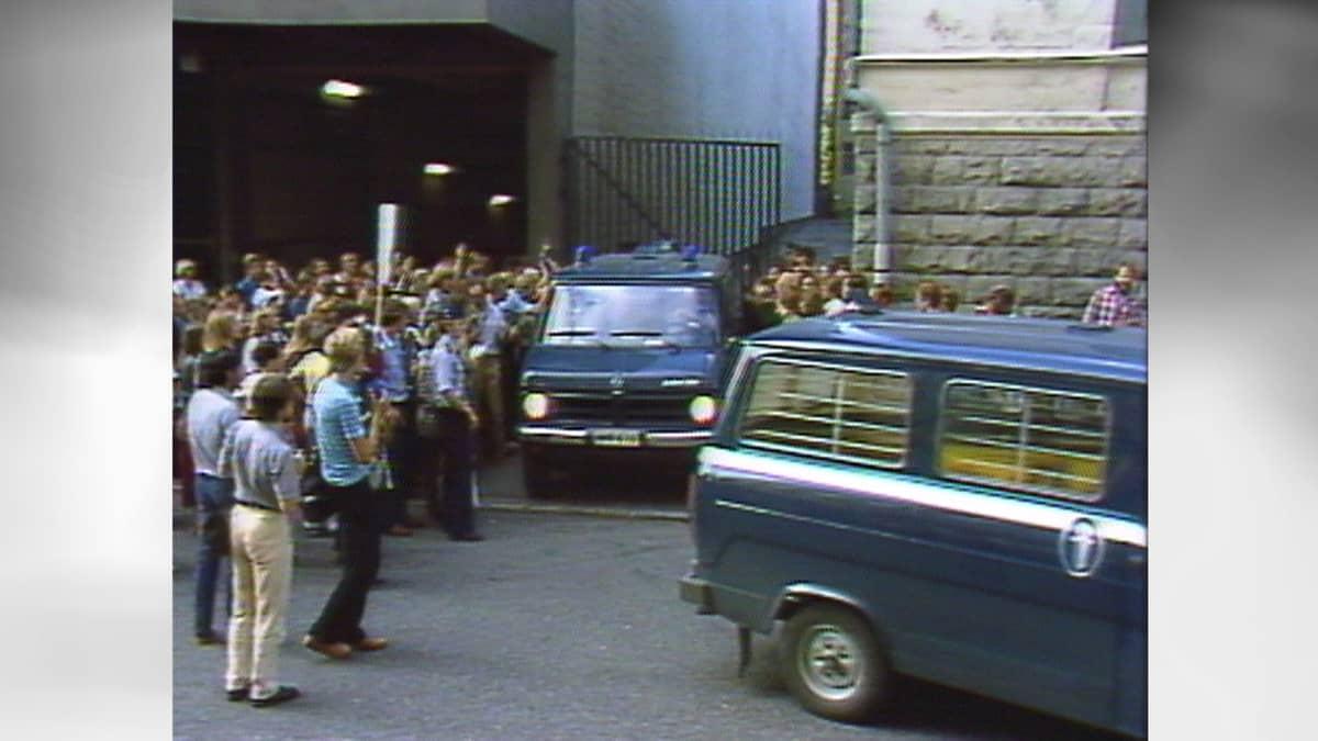 Mielenosoittajia ja kaksi poliisiautoa.