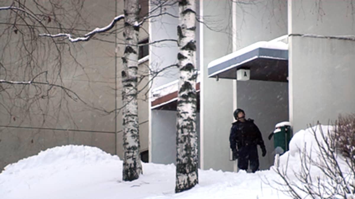 Poliisi eristetyn kerrostalon pihalla Espoon Suvelassa.