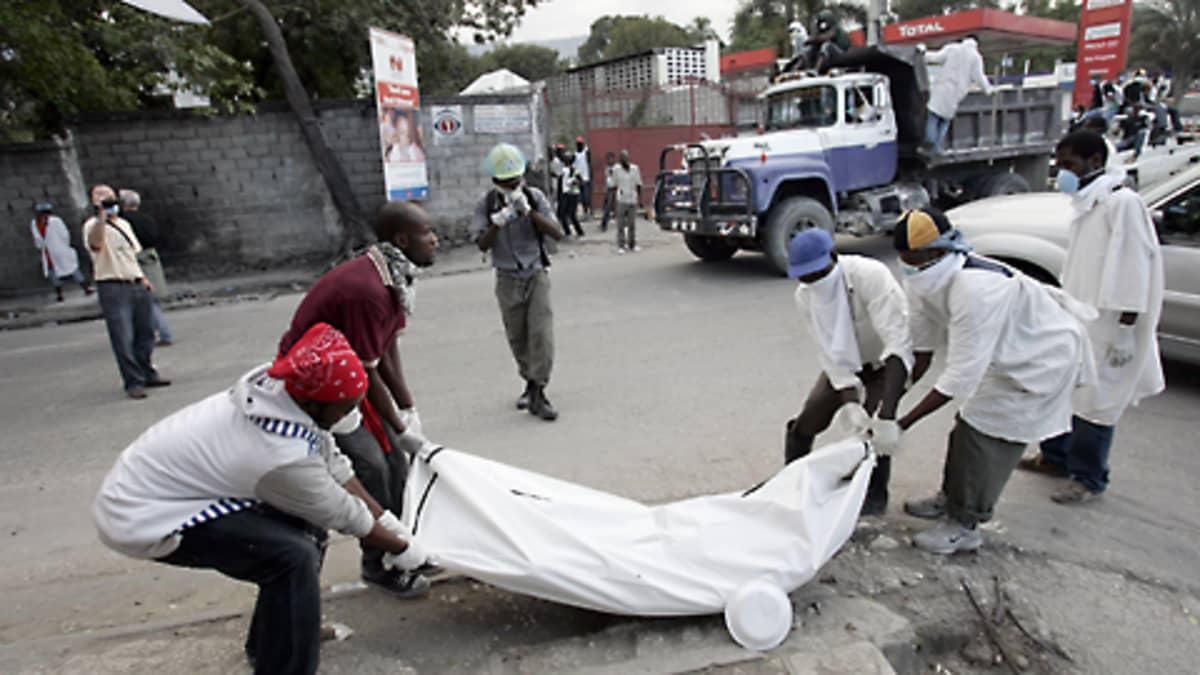 Vapaaehtoistyöntekijät nostavat ruumissäkkiä Port-au-Princen kadulla