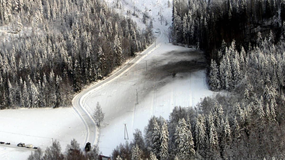 Ilmakuva aukeasta metsänreunassa, johon Hornet-hävittäjä oli syöksynyt. Tuilpalossa mustunutta lunta. Tie kulkee metsänreunan ohi.