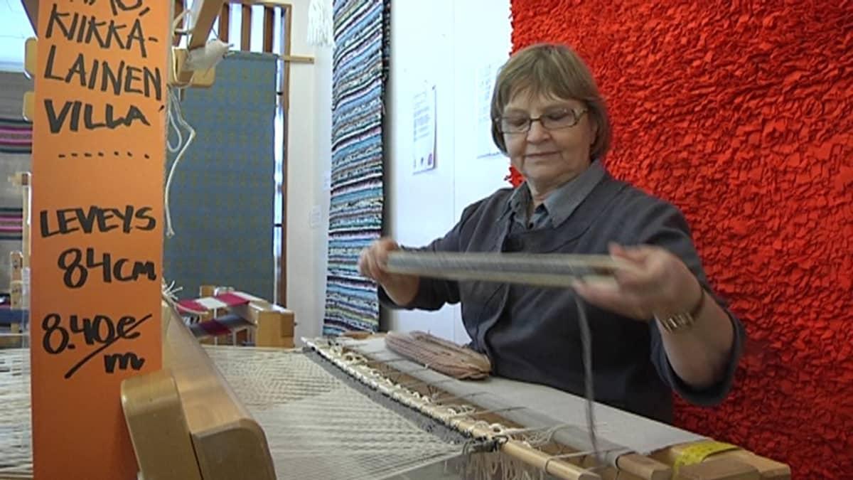 Birgit Kinnanen kutoo mattoa.