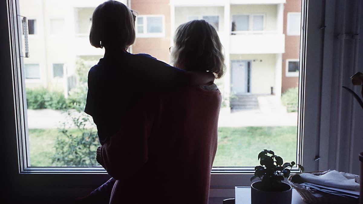 Äiti pitelee lasta sylissään ikkunan ääressä