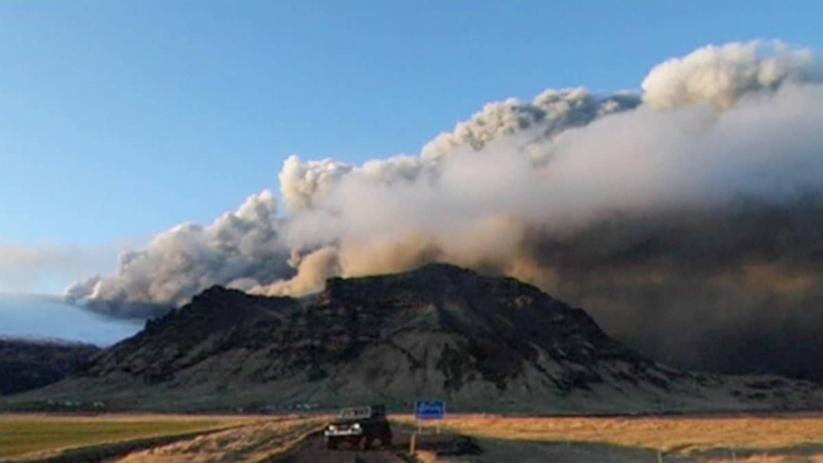 Savua päästelevä tulivuori, etualalla jeeppi