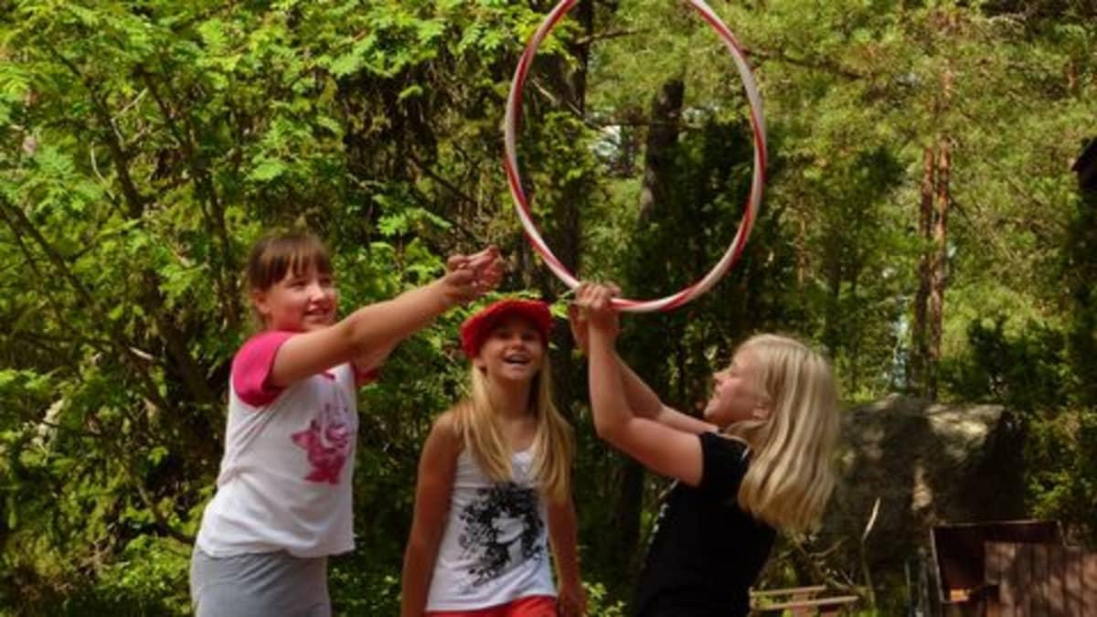 Tytöt leikkivät vanteella.