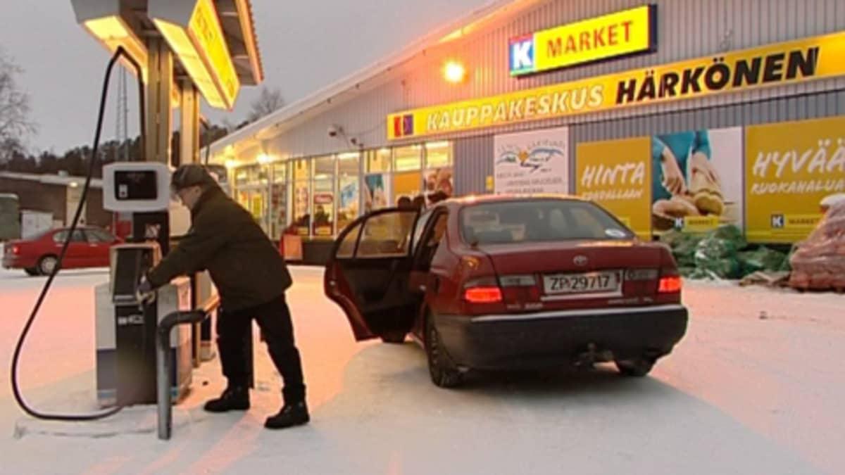 Mies tankkaa autoa kaupan pihalla.
