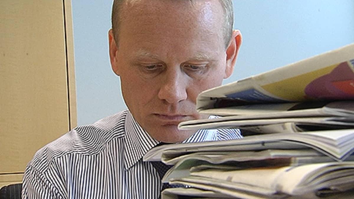 AKT:n puheenjohtaja Timo Räty työpöytänsä ääressä. Edessään korkea pino lehtiä.